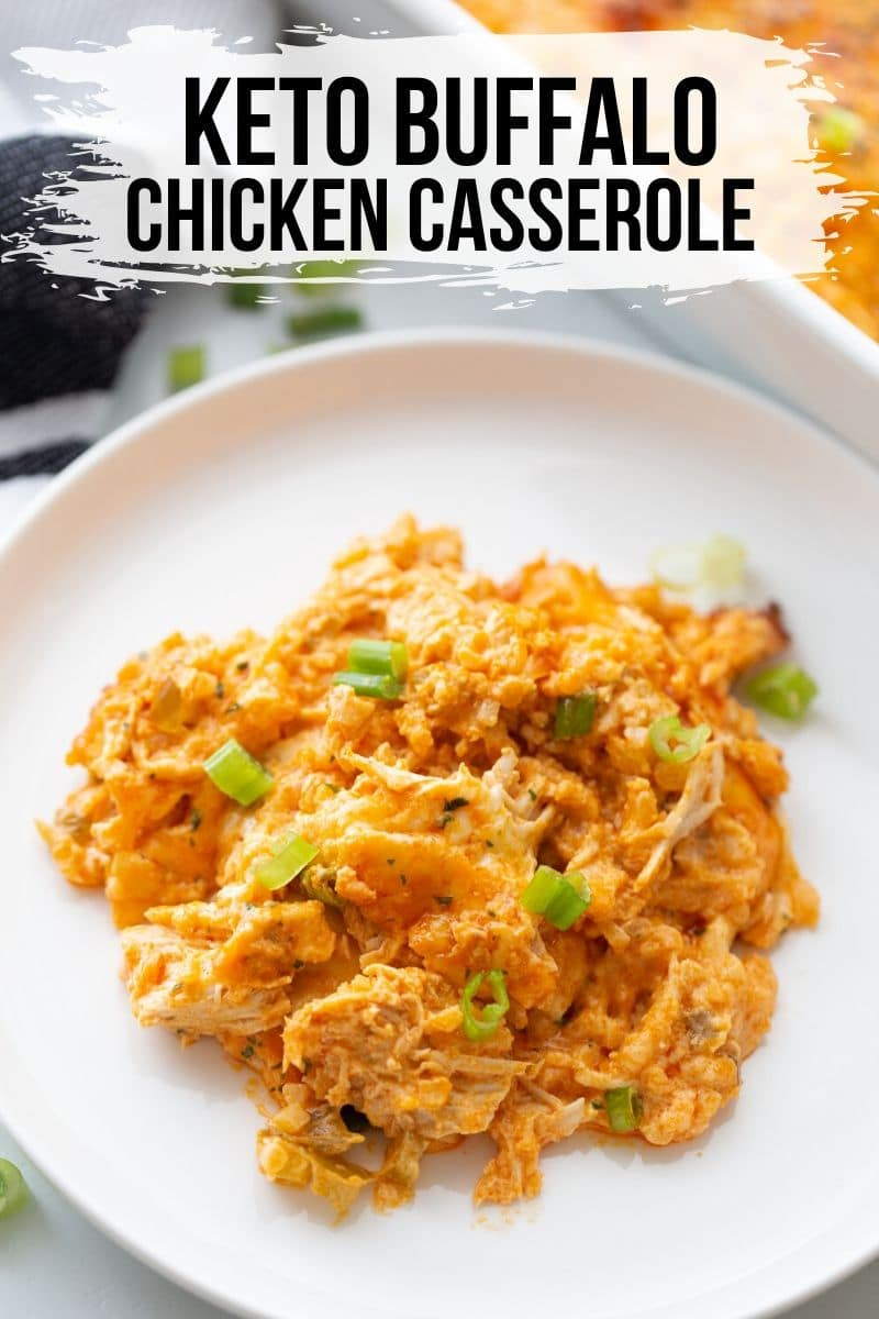 shredded chicken covered in a cheesy buffalo sauce with scallions on a white plate