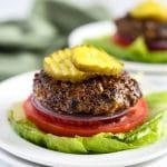 keto stuffed burger plated with lettuce, onions, tomatoes, and pickles on top