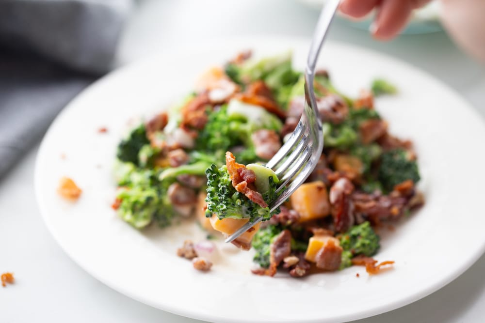bacon cheese and broccoli salad on a fork with plate in background