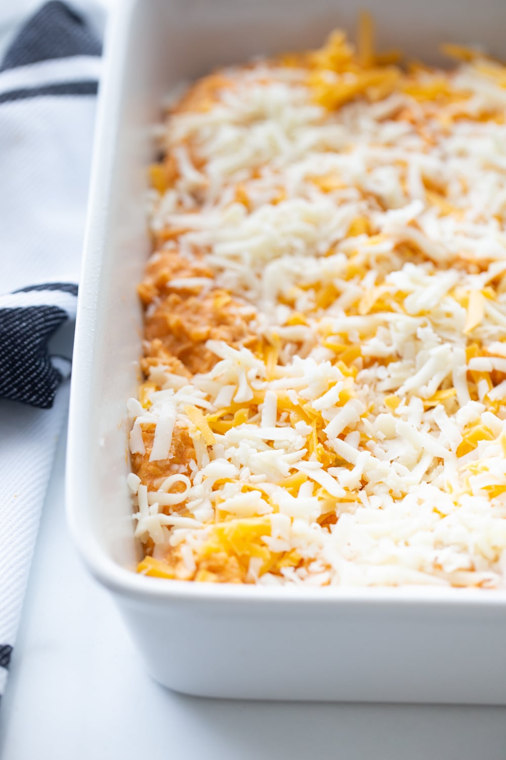 Shredded chicken covered in shredded cheeses in a white casserole dish.