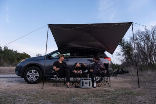MoonShade attached to the side of a car with people sitting under it