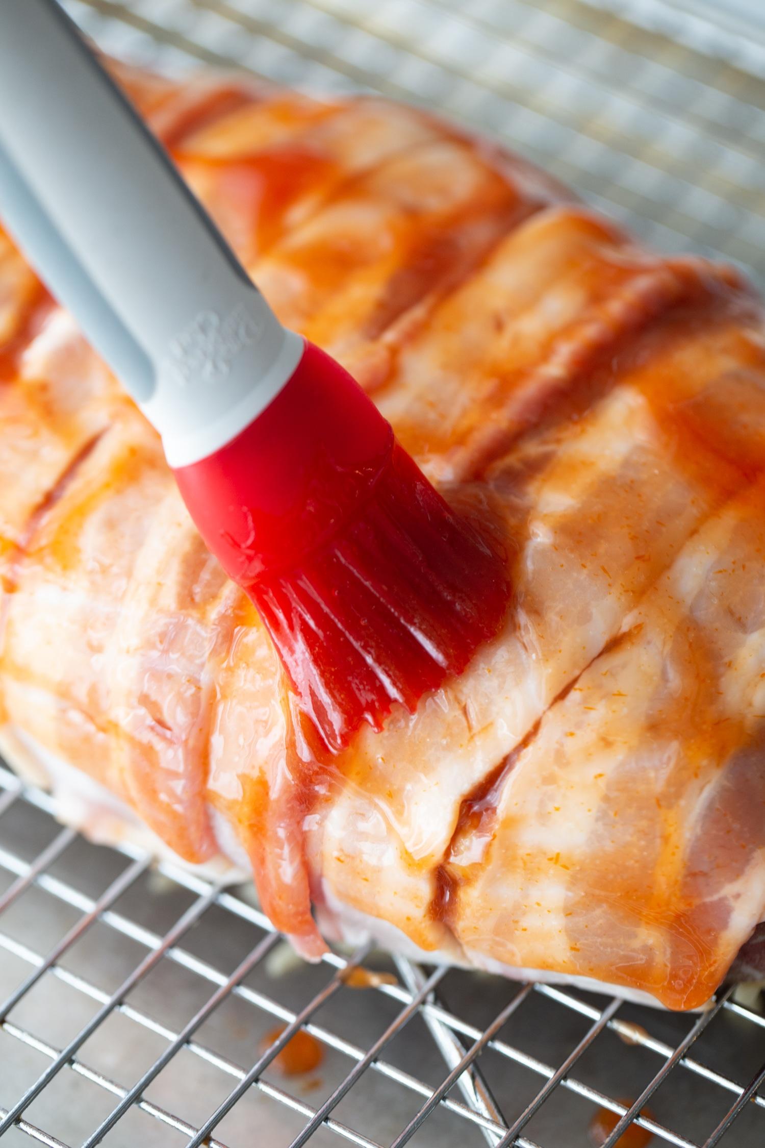 keto meatloaf glaze being brushed onto meatloaf