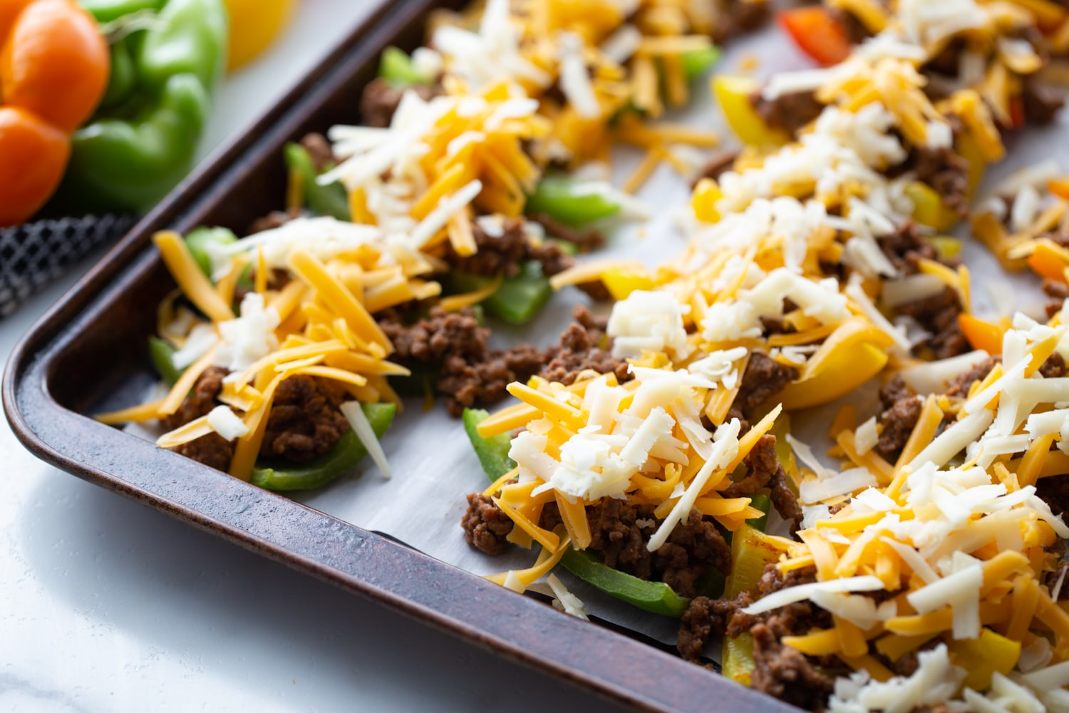bell pepper slices stuffed with ground beef topped with shredded cheese
