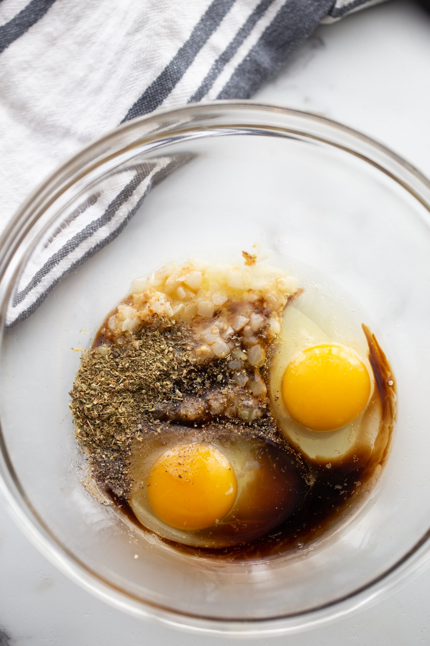 eggs, parmesan cheese, worcestershire sauce, onions, garlic, spices in a clear bowl