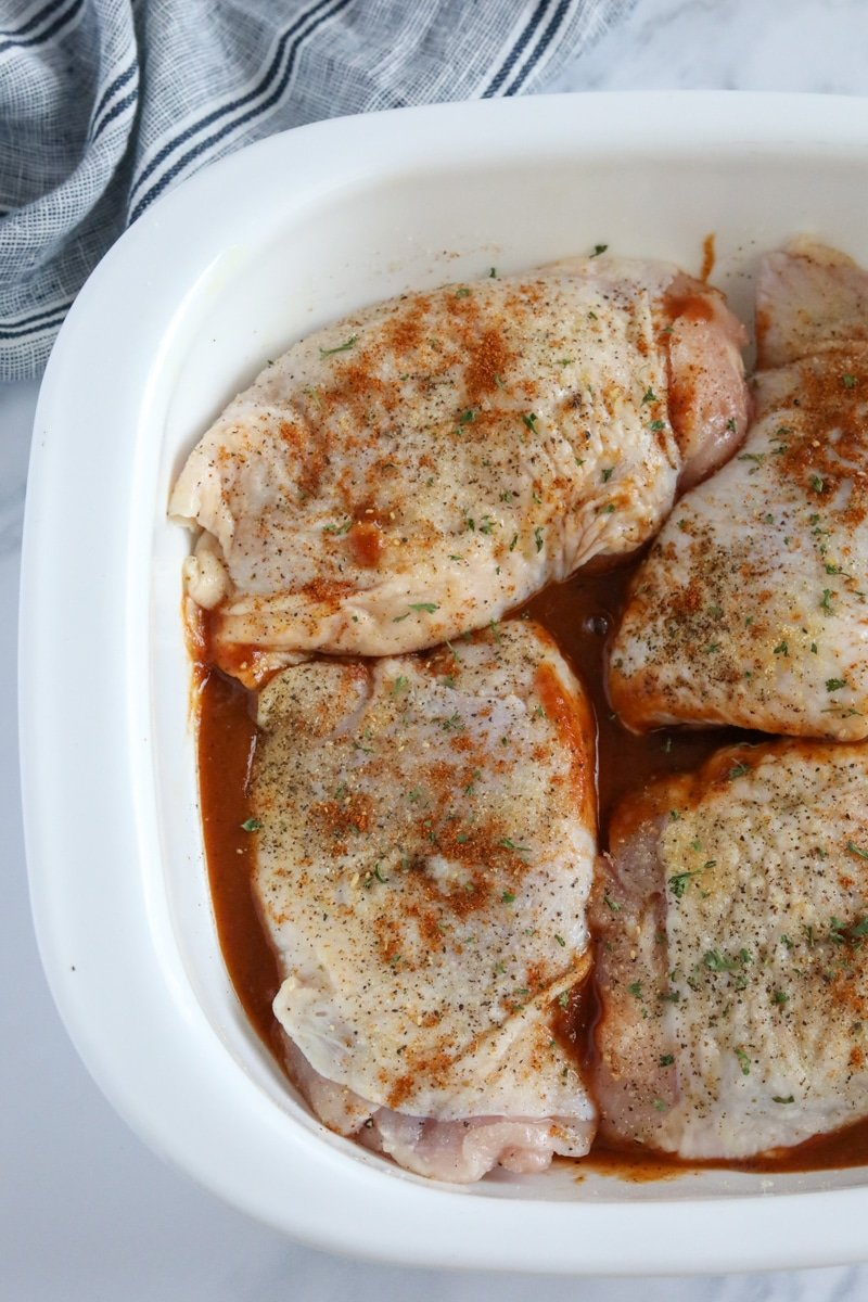 raw chicken thighs over top of BBQ sauce in a casserole dish