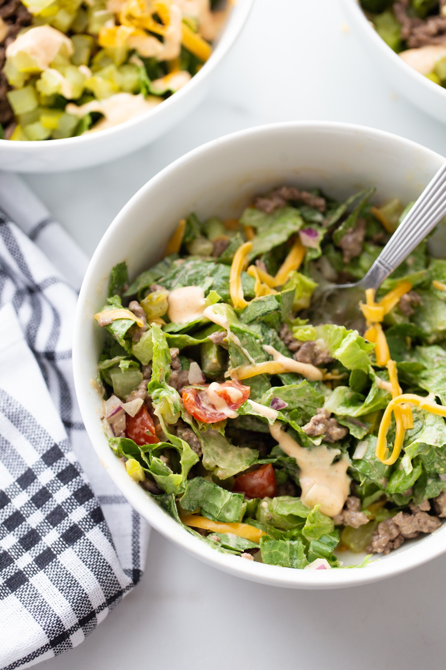big mac burger salad in a bowl with lettuce, cheddar cheese and veggies