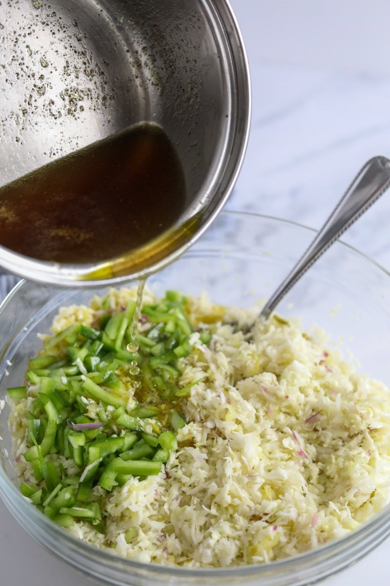 hot vinegar, sweetener, pickle juice and spices being poured over top of cabbage