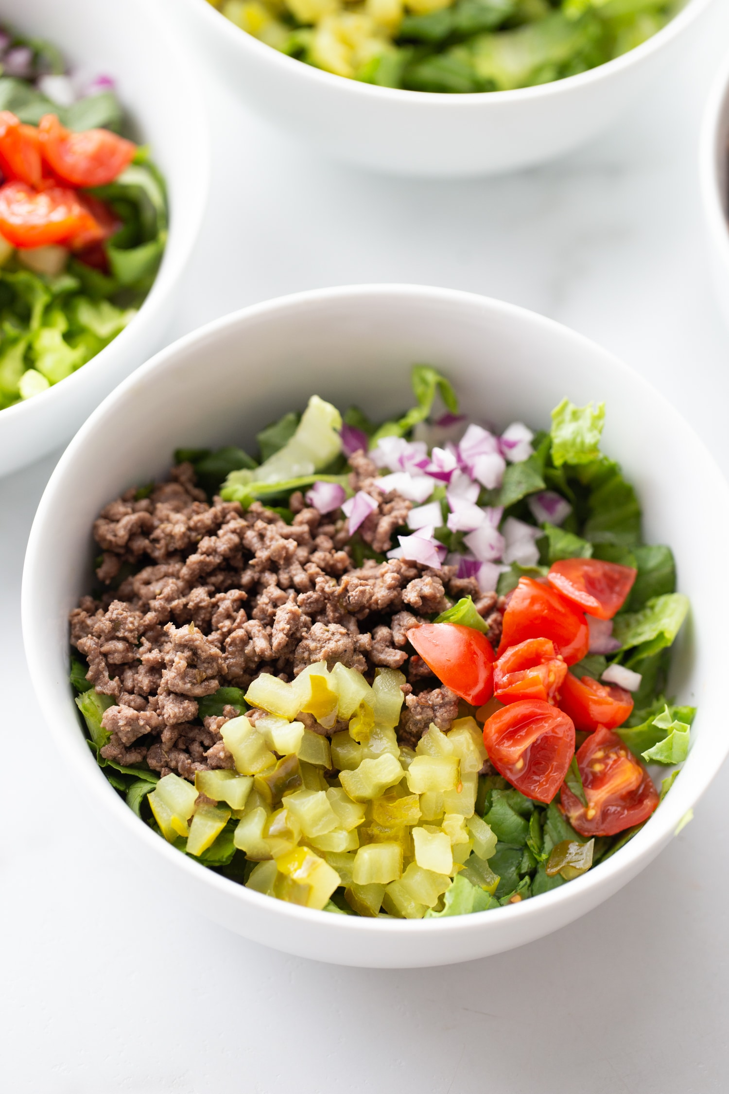 big mac ground beef, tomatoes, onions and peppers in a bowl on top of lettuce