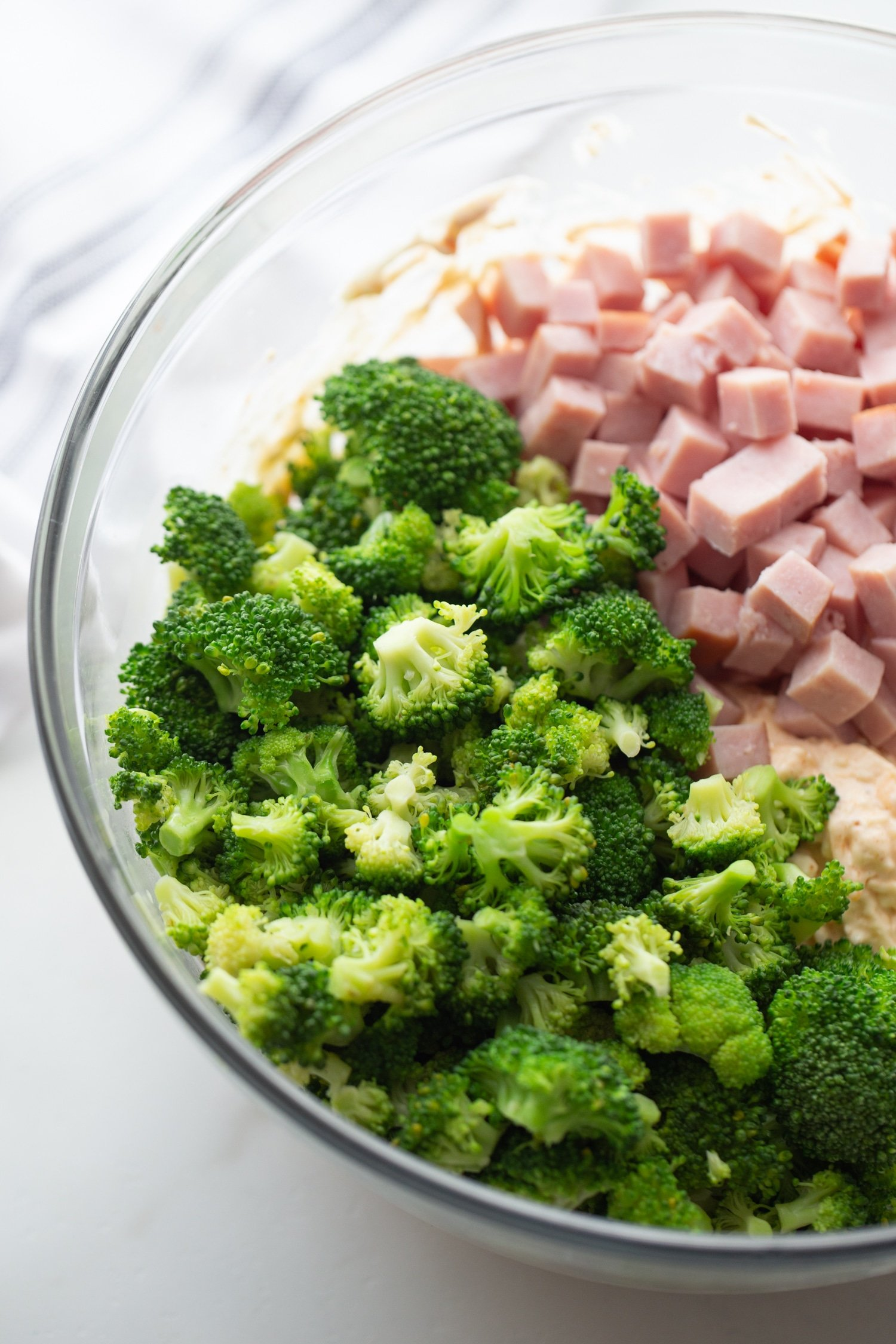 fresh broccoli florets with diced ham and cheeses in a bowl