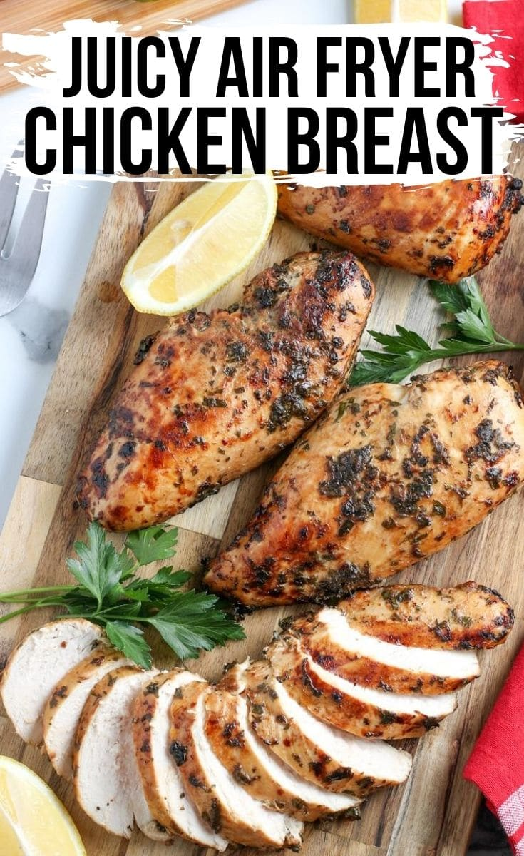 marinated chicken breasts sliced on a cutting board with lemon wedge