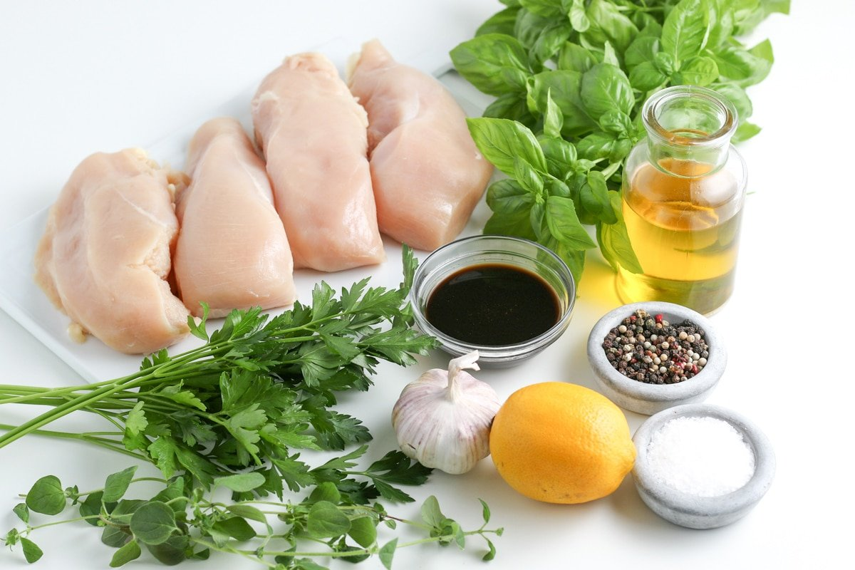 boneless skinless chicken breasts, fresh herbs, lemon, spices, garlic and oil on a table