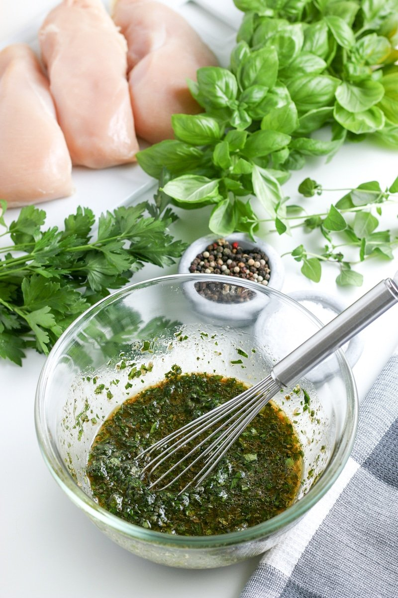 chicken marinade in a bowl with a whisk with fresh herbs on a table