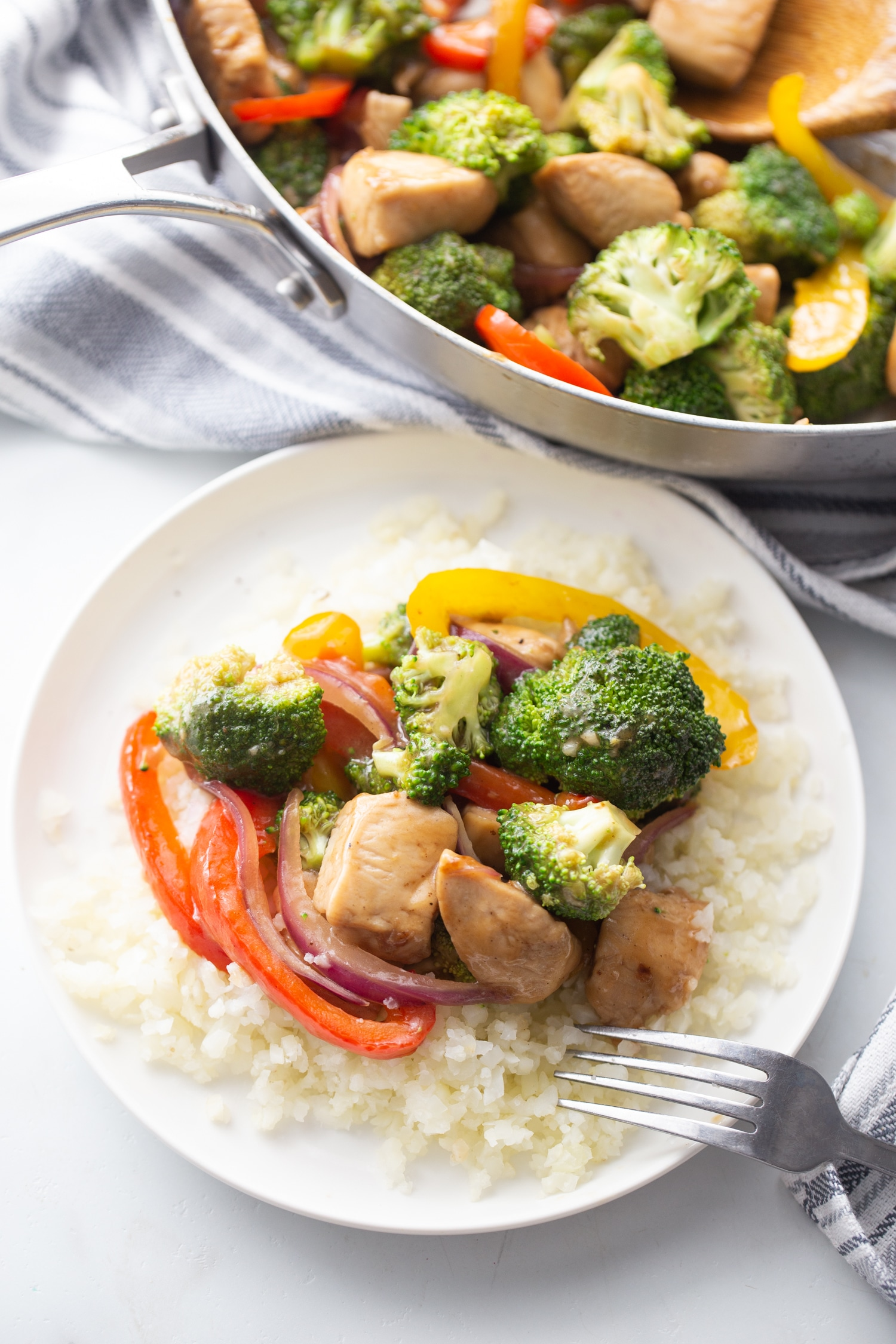 keto stir fry chicken over a bed of steamed cauliflower rice