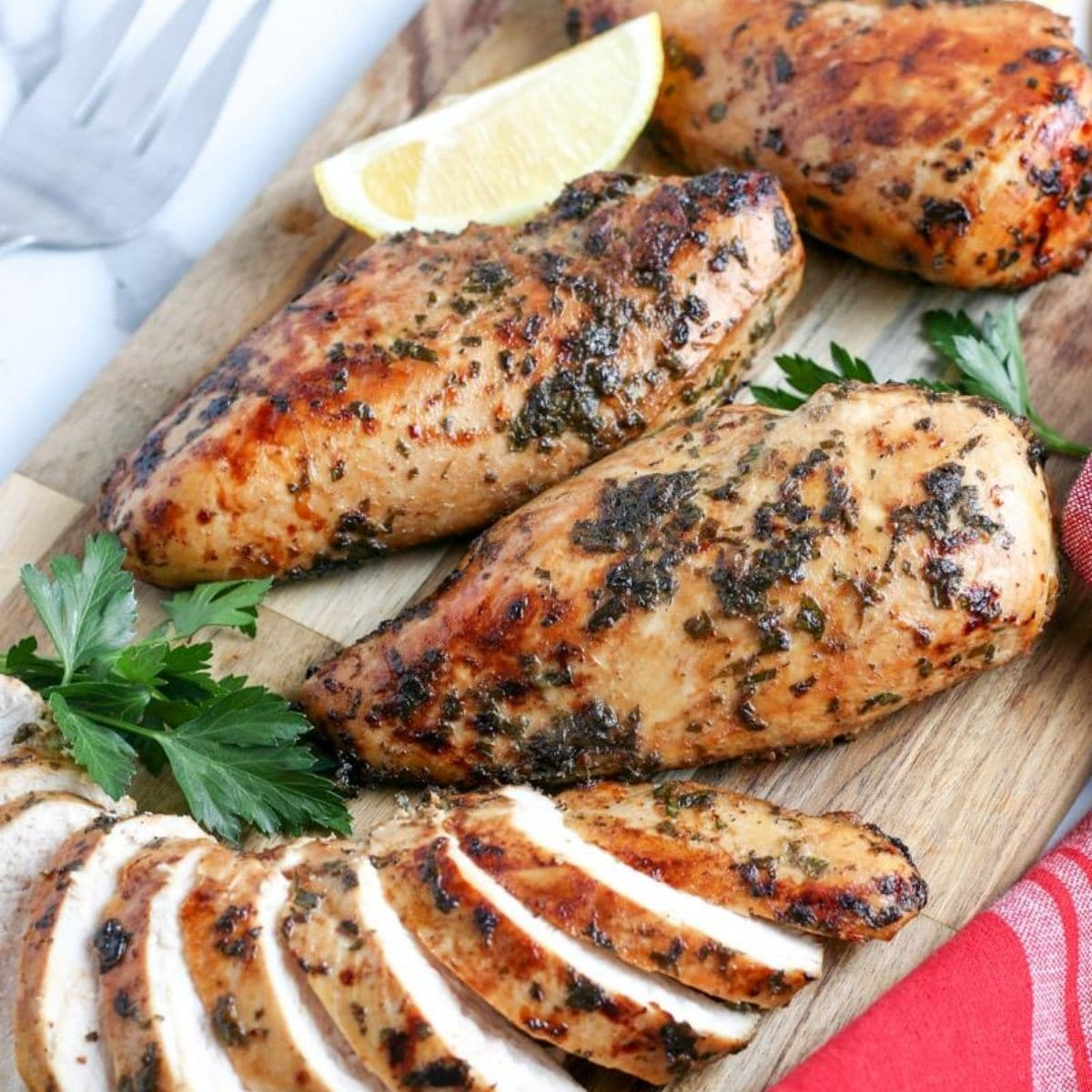 sliced air fyer chicken breasts on a cutting board with lemon and herbs
