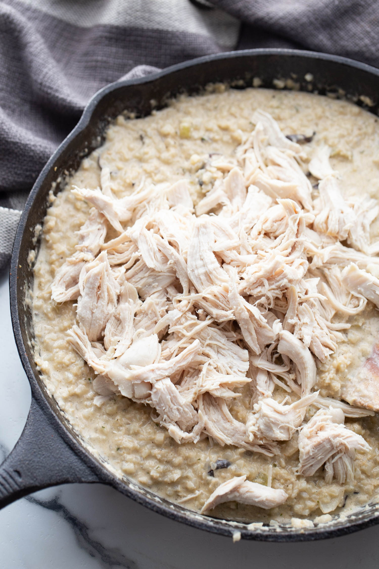 shredded chicken on top of cream, mushrooms and veggies in a skillet