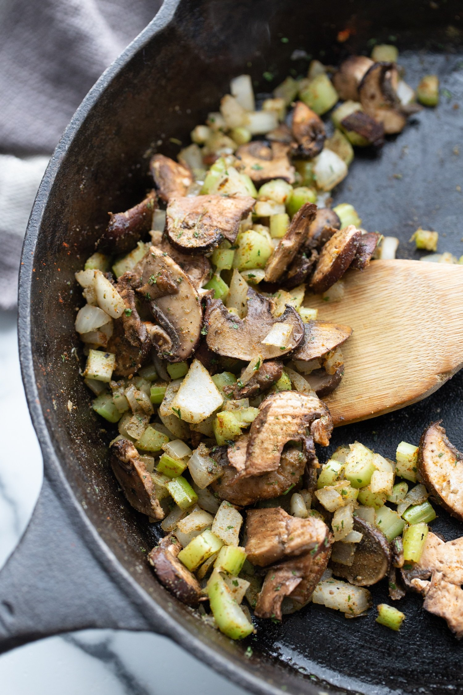 celery, onions and mushrooms in a skillet