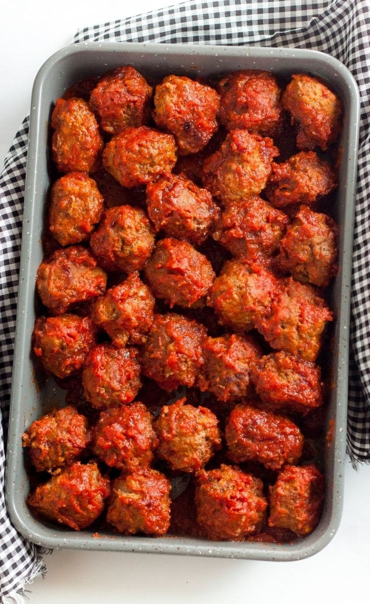 Meatballs covered in sauce, sitting in a pan