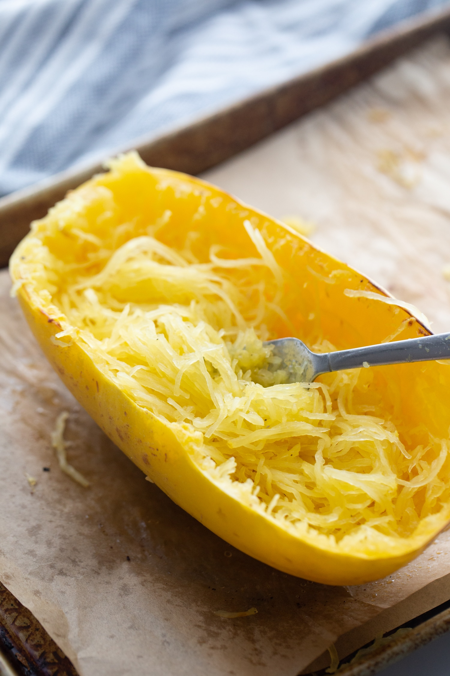 roasted spaghetti squash cut open with a fork in half of it.