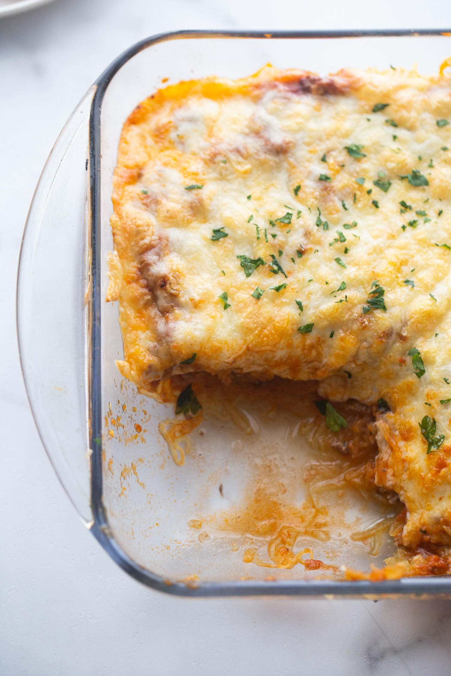 low carb baked italian casserole in a glass baking dish with a piece cut out