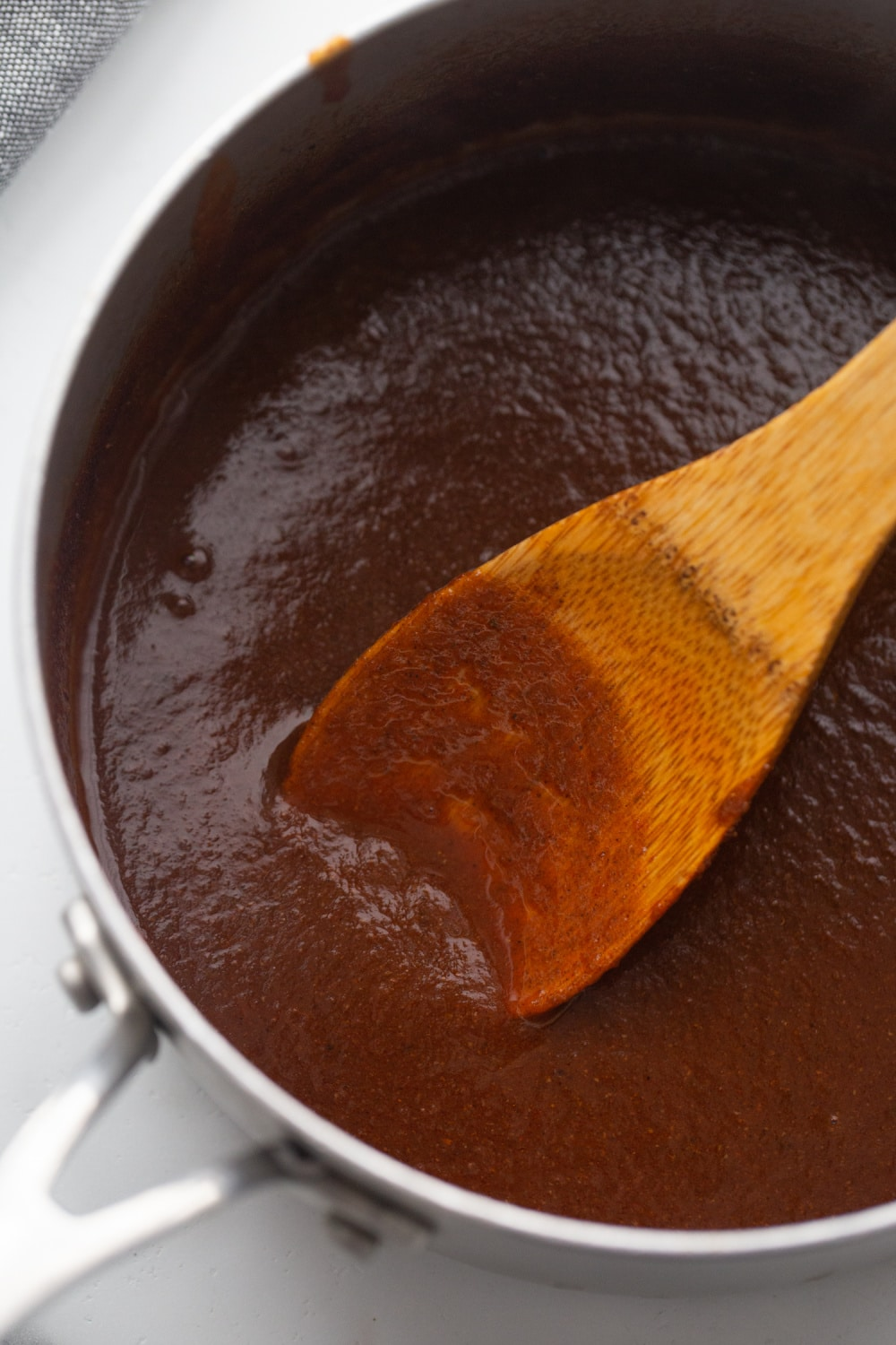 homemade low carb enchilada sauce in a skillet with a wooden spoon