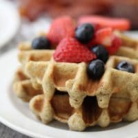 keto waffle on a white plate with strawberries and blueberries on top